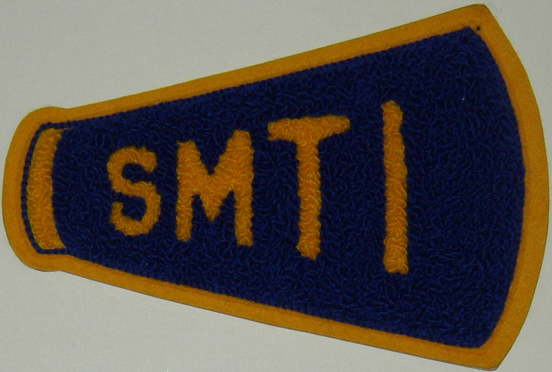 Photograph of an SMTI cheerleader's patch in the shape of a bullhorn